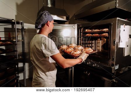 Handsome baker in uniform holding tray full of freshly baked bread at the manufacturing.the Baker taking fresh bread