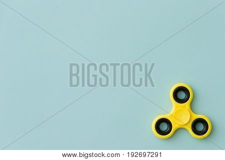 Yellow fidget spinner device on turquoise background. Top view. Playing with a yellow hand spinner fidget toy