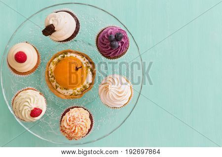 Top view on homemade vanilla blueberry lemon chocolate cupcakes on cristal plate on turquoise retro wooden background. Healthy food snack for birthday party or celebration