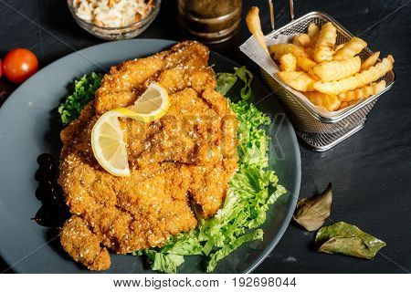 Details Of Delicious Dinner - French Fries And Coleslaw With Parmesan Grilled Schnitzel