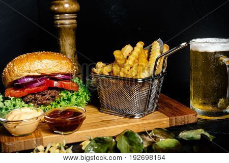 Tasty Grilled Beef Burger Served With Fries And Lettuce On Wooden Board At Local Pub