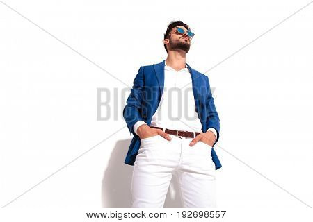 elegant young man wearing sunglasses standing with hands in pockets and looks away on white background