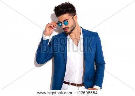 side view portrait of a young elegant man putting on his sunglasses on white background