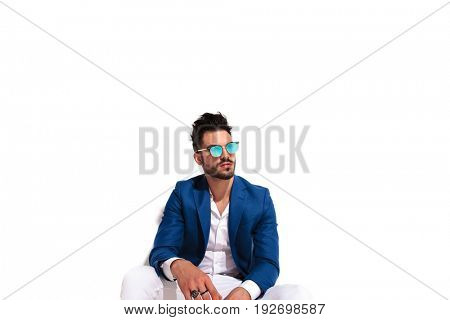 fashion model in elegant clothes and sunglasses sitting and looks away from the camera on white background