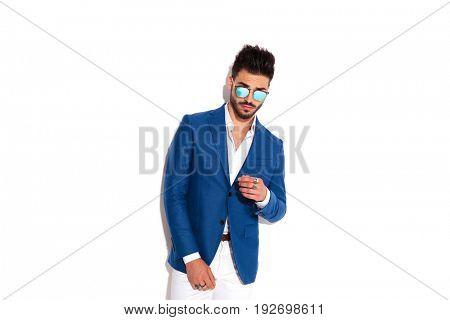 sexy elegant man wearing sunglasses posing on white background