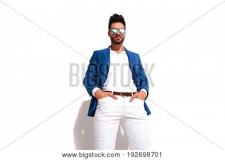 smart casual man standing with hands in pockets looks down to the camera on white background