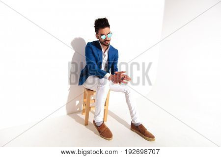 side of a fashion man sitting on chair and rubbing his hands while looking away from the camera on white background