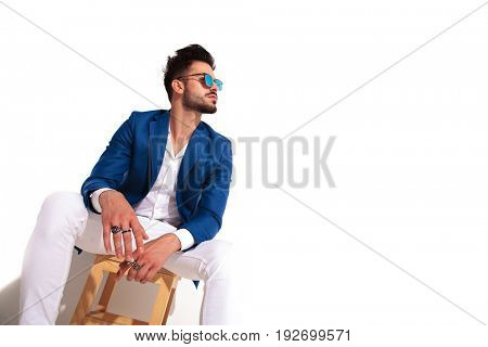 seated fashion young man is looking up to something on white background