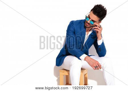 side picture of a seated fashion man taking off his sunglasses and looks away from the camera on white background