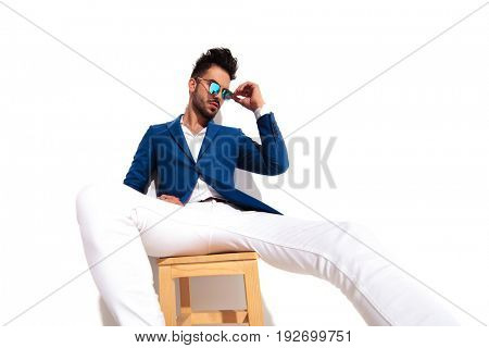 sexy young man in suit putting on his sunglasses while seated on chair on white background