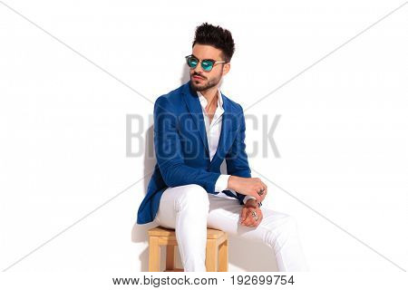 elegant young man wearing sunglasses is resting on a chair and looks to side on white background