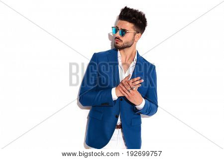 elegant man rubbing his palms and looks to side on white background
