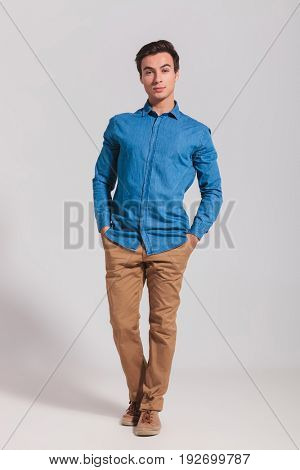 full body picture of a casual man standing with hands in pockets on grey background