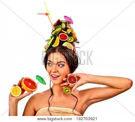 Girl drinking fruit cocktail on summer party. Woman with fresh fruits hairstyle and bare back hold halves of grapefruit with cocktail umbrella. Concept of fresh juice in nonalcoholic drink bar on