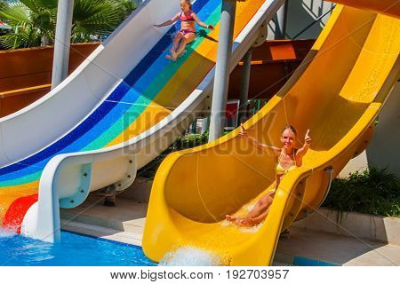 Swimming pool slides for children on water slide at aquapark and thumb up. Summer holiday mood outdoor. Happy childhood of there are two kids girl sisters in aqua park. Summer vacation for kids.