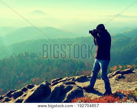 Photographer  On Cliff. Nature Photographer Takes Photos With Mirror Camera On Peak