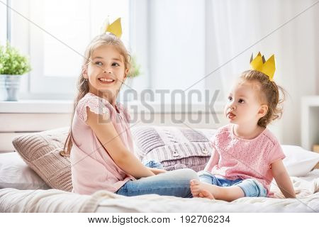 two cute children baby girls playing and having fun in the kids room. loving sisters with crowns on the bed.