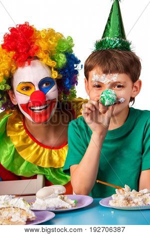 Birthday child clown eating cake with girl together. Kid with messy face have tier cake fight on isolated. Boy plays with food.