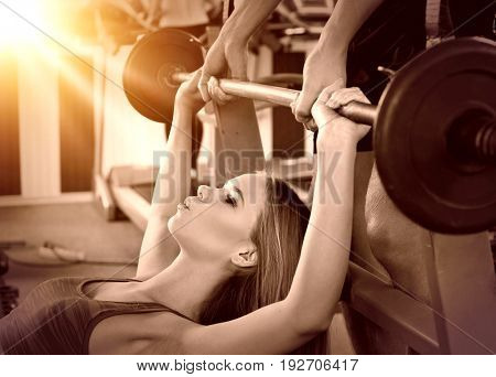 Woman with barbell at sport gym. Girl working on bench press. She lifting barbell. Cropped shot of man backs girl while taking exercises. Color sepia tone on shiny sunlight background.