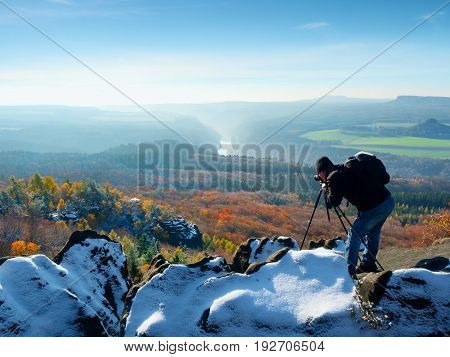 Professional Photographer Takes Photos With Mirror Camera And Tripod On Snowy Peak