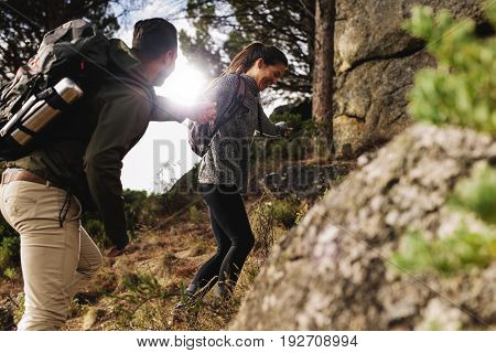 Happy Young Couple Hiking Together In Mountain