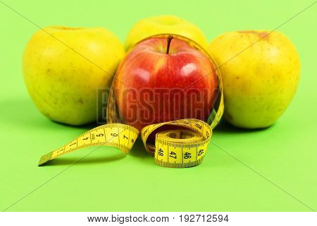 Apples With Yellow Measuring Tape In Roll Isolated On Green