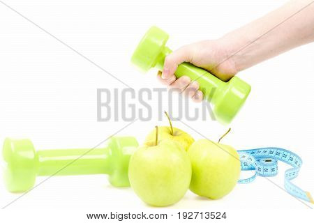 Hand Holding Green Dumbbell And Apples With Another Lightweight Equipment