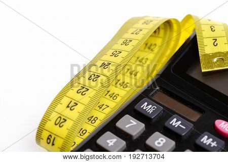 Calculator and yellow measuring tape isolated on white background defocused parts. Concept of counting calories