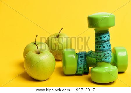 Dumbbells In Green Color Wrapped With Cyan Blue Measuring Tape