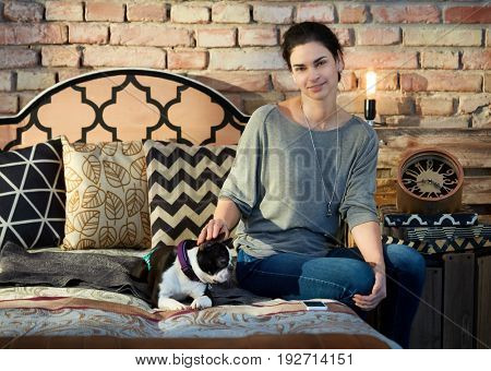 Woman sitting on bed at home in loft apartment fondling dog, smiling.