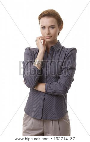 Portrait of attractive young businesswoman looking at camera, hand on chin.