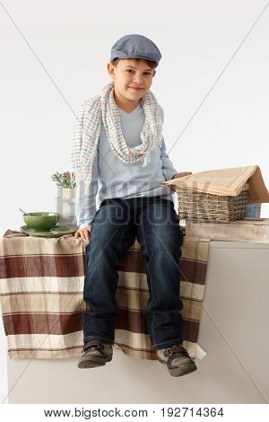Cute little schoolboy sitting at home on kitchen counter, reading newspaper.