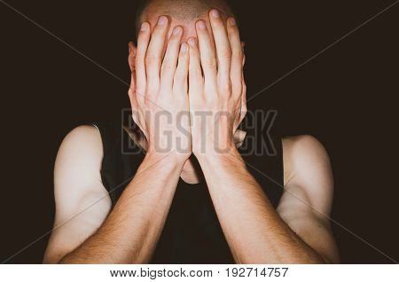 Depression. Depressed man cover his face with his hands. Isolated on black background.