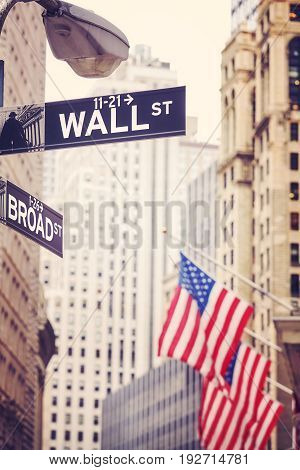 Wall Street And Broad Street Signs With American Flag In Distance, Nyc.