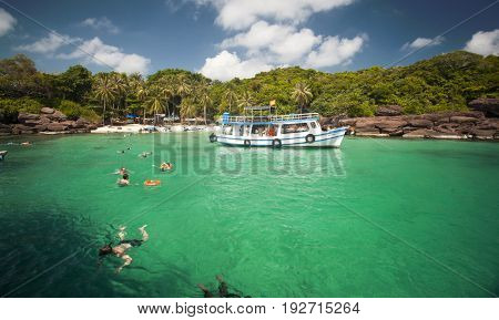PHU QUOC, VIETNAM - March 22, 2017: Snorkeling divers near a remote tropical island with palm trees and blue ocean near Phu Quoc, Vietnam