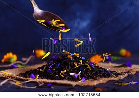 Black tea with flower petals and citron on a metal spoon close up