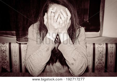 Depression. Depressed woman with cigarette cover her face with her hands. Sadness. Loneliness.