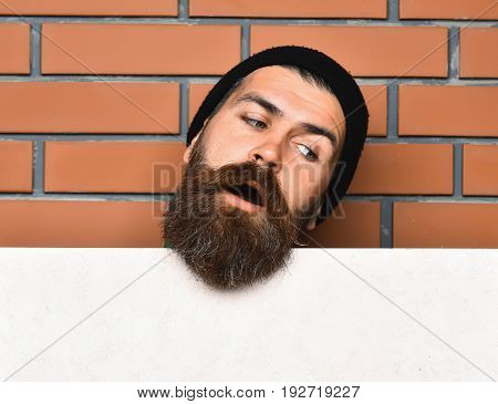 Bearded man long beard. Brutal caucasian surprised unshaven hipster in black hat with white paper sheet on brown brick wall studio background copy space