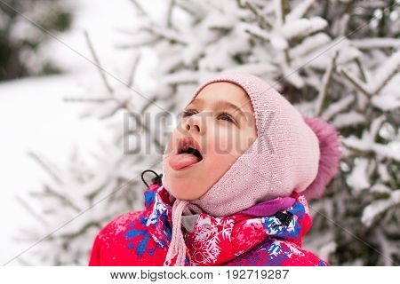Portrait Of Little Cute Baby Russian Girl Catches Snowflakes In Her Mouth In Winter Parke Close Up.