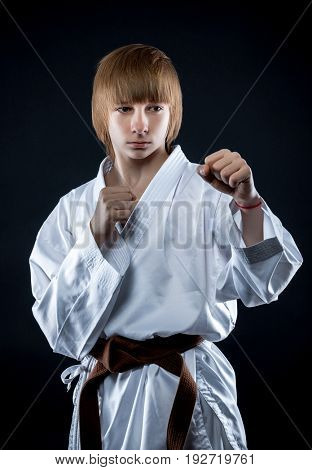 Portrait of a young athlete in a kimono on a dark background