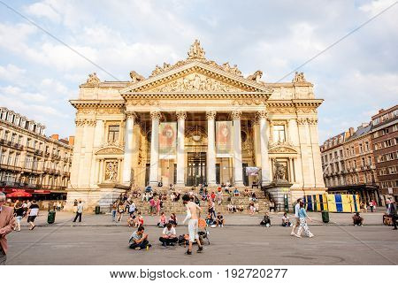 BRUSSELS, BELGIUM - June 01, 2017: Sunset view on the crowded square near the building that houses Brussels Stock Exchange in the center of the old town of Brussels, Belgium