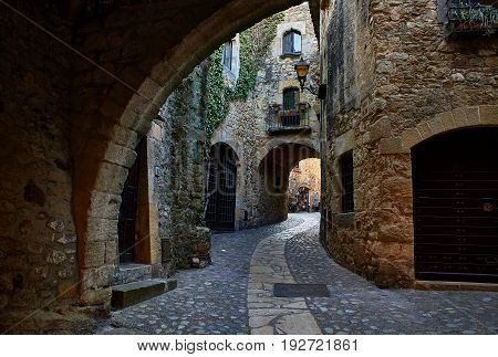 Pals Spain - June 22 2017. Doorgang of Carrer Major street in the medieval historic downtown of Pals. Bajo Ampurdan Girona Catalonia Spain. poster