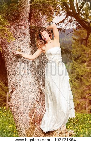 Young blonde woman standing in wedding dress on a tree