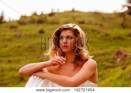 Portrait of a young blond bride smoking.