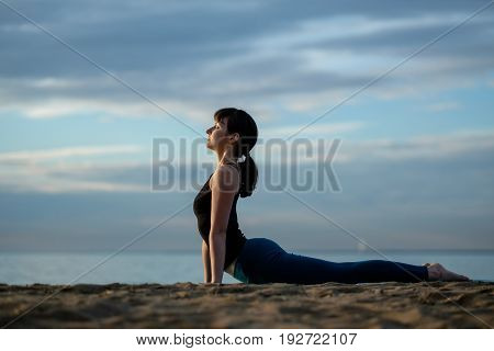 Yoga asana outdoors on beach. Caucasian woman practices Ashtanga Vinyasa yoga Surya Namaskar Sun Salutation Urdhva Mukha Svanasana. Upward facing dog pose