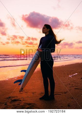 Silhouette of slim girl in wetsuit with long hair and surfboard on beach at warm sunset or sunrise. Surfer and ocean