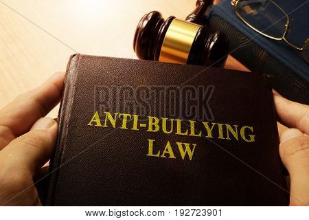Hands holding Anti-Bullying Law in a court.