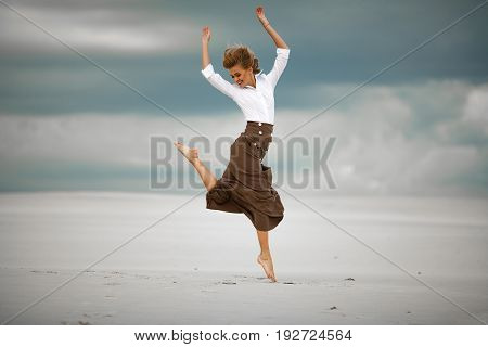 Young woman jumps on sand in desert. She is dressed in long skirt and blouse and joyful laughs.