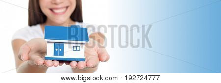 Real estate house banner with blue copy space panorama. Woman smiling showing miniature toy home holding hands for home insurance protection concept.
