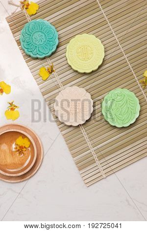 Sweet color of snow skin mooncake. Traditional mid autumn festival foods with tea on table setting.